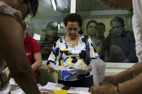 Election officials count votes watched by the public at a polling station in Havana