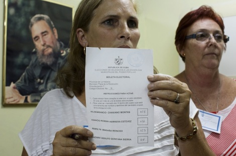 An election official (C), shows the results of a polling station after counting the votes beside a picture of Cuba's former president Fidel Castro in Havana